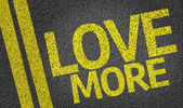 Love More written on the road — Stock Photo