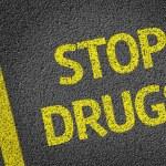 Постер, плакат: Stop Drugs written on the road