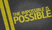 The Impossible is Possible written on the road — Stock Photo