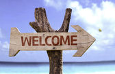 Welcome wooden sign with a beach on background — Stock Photo