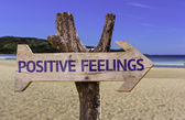 Positive Feelings wooden sign with a beach on background — Stock Photo