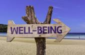 Well-Being wooden sign with a beach on background — Stock Photo