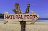 Natural Foods wooden sign with a beach on background — Stock Photo