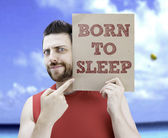 Man holding a card with the text Born to Sleep — Stock Photo
