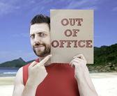 Man holding a card with the text Out Of Office — Stock Photo