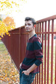Young hansome man standing near the fench in colorful autumn garden — Stock Photo