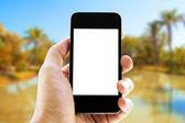 Hand halten Telefon mit Strand-Hintergrund — Photo