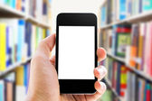 Hand holding smart phone on library background — Stock Photo
