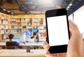 Hand holding smart phone on library background — Foto de Stock