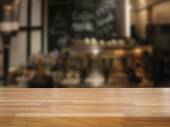 Mpty wooden table and blurred cafe background — Stock Photo