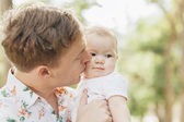 Close-up Father kissing his cute baby  outdoors in spring park a — Stock Photo