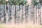 Old wooden fence with barbed wire on top. Vintage. — Stock Photo
