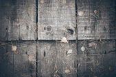 Old wooden planks covered with leaves. Retro grainy film look. — Stock Photo