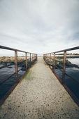 Старый мост с ржавыми металлическими рельсами. ретро зернистый взгляд фильма. — Стоковое фото