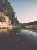 River with reflections in weater and sandstone cliffs - retro, v — Stock Photo
