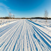 Snowy winter road with tire markings — Stock Photo