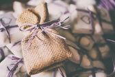Purple raffia, confetti and jute sachet — Stock Photo