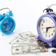 Two of old style alarm clocks on top of pile of banknote and coi — Stock Photo #58905059