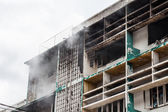 Fire burning building with smoke pouring out — Stock Photo