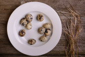 Quail eggs on plate rustic wooden background with straw — Stock Photo