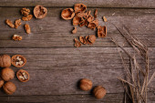 Walnuts on rustic wooden board background with straw copy space for text — Stock Photo