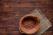 Wooden table with basket on burlap texture background — Stock Photo