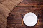 Empty white plate with fork and knife on rustic wooden background  — Stock Photo
