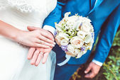 Newlyweds couple holding hands with rings and wedding bouquet — Stock Photo
