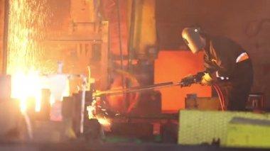 Worker cuts fiery steel blocks — Stock Video