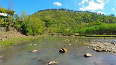 River flows near village with forest on hill — Stock Video