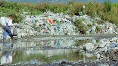 Man walking through Garbage in the river — Stock Video