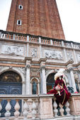 Early morning in Venice, a mask sit down under the tower — Stock Photo