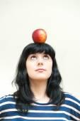 Pretty brunette girl looking red apple on head — Stockfoto