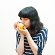 Brunette girl smells apple and orange in her hands — Stock Photo #63343149