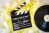 Clapper board with 35mm film yellow frames and movie reel — Стоковое фото