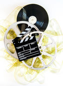 Movie clapper on 35mm yellow unrolled film and cinema reels — Stock Photo