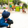 Little baby on stroller looking at games in city garden — Stock Photo #71928529