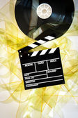 Movie clapper on 35 mm cinema reel unrolled yellow filmstrip — Stock Photo