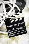 Movie clapper on 35 mm cinema reels unrolled filmstrip — Stock Photo