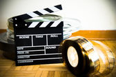 Movie clapper board and 35 mm film reel on wooden floor — Stock Photo