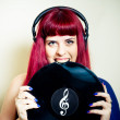 Young pretty woman smiling and biting vinyl record close up — Stock Photo #79212526