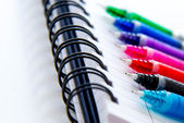 Back to school supplies, multi colored pens and a spiral noteboo — Stok fotoğraf