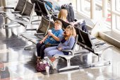 Passengers waiting in front of a bright interior airport window — Stock Photo