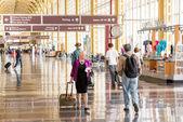 Passengers walking through a bright airport — Stockfoto