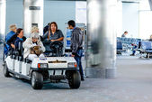 People and passengers riding in motorized carts in the airport — Stok fotoğraf