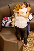 Women hugging goodbye in an airport waiting area — Stock Photo