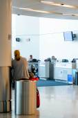 Woman seated on a trash can waiting for her flight in an airport — Stock Photo