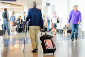 Passengers walking with luggage in an airport — Stock Photo