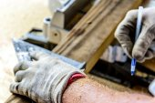 Man wood working table saw with hands and glove — Stockfoto