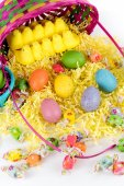 Easter basket with colored eggs, yellow chicks and candy — Stock Photo
